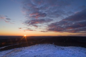 Sun sets over distant hills with snow in the foreground