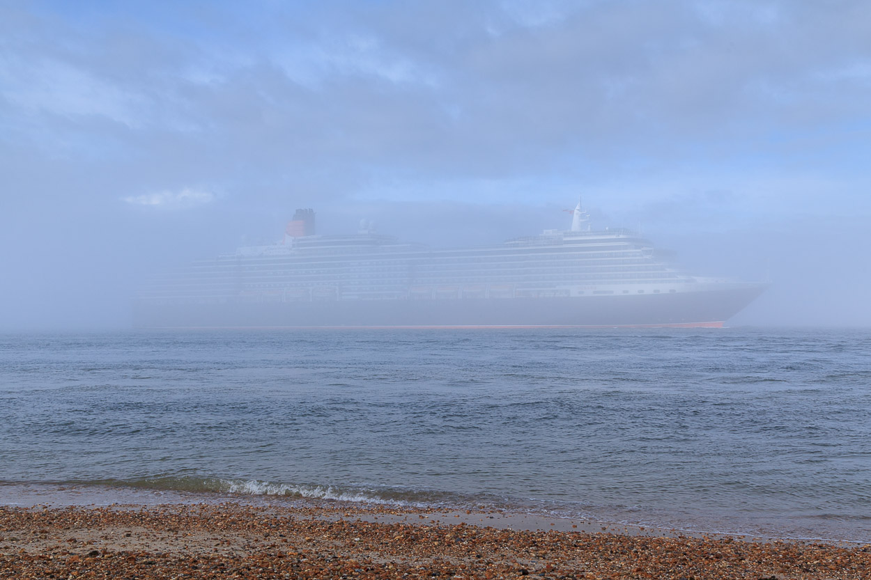Queen Elizabeth steaming down Southampton Water past Calshot Castle in fog.