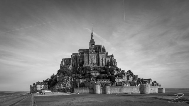 Black and white image of the Mont St.Michel at dawn, with delivery trucks near its entrance