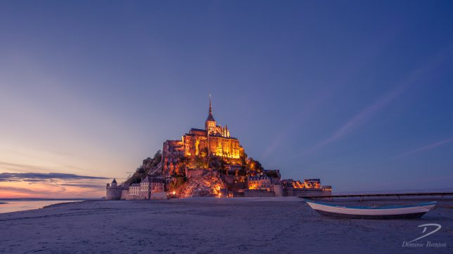 Wide-angle photo of Mont St. Michel at dusk (blue hour) with a small boat in the foreground