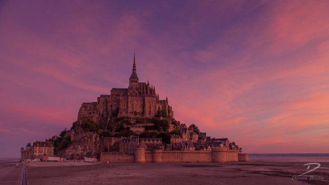 Mont St. Michel at dawn with delivery vans parked outside