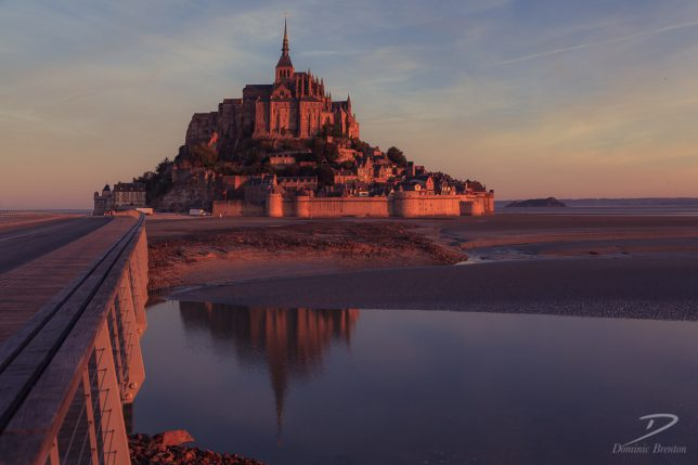 Mont St. Michel at sunrise casts reflections in the estuary that surrounds it