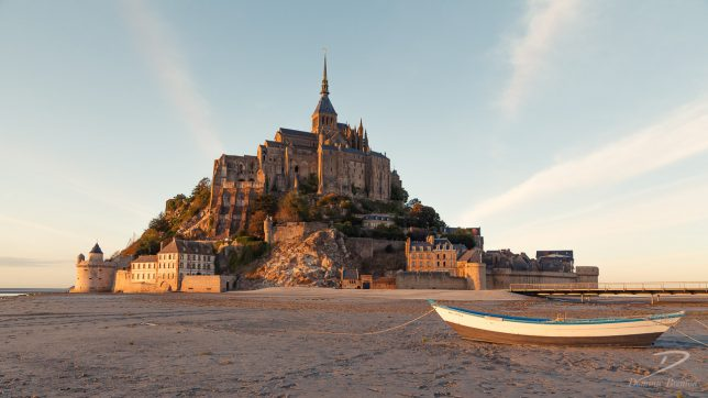 Mont St. Michel during golden hour with a rowing boat in the foreground