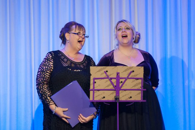 Two women singing duet in evening dress