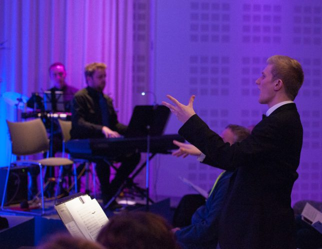 Blond man conducting with pianist in background